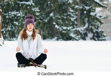 woman meditating at the park in winter