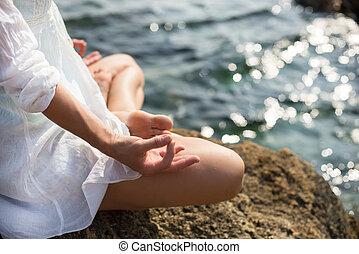 Woman meditating at the sea - serenity and yoga practicing ...