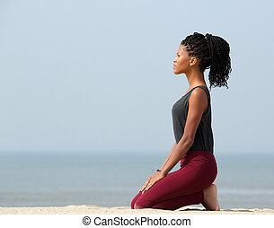 Woman meditating at the seaside