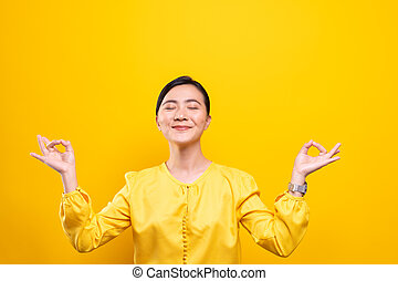 Woman meditating holding her hands in yoga gesture on isolated yellow background
