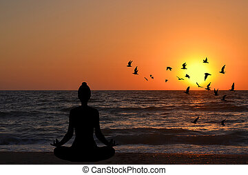 Woman meditating in a yoga pose on the beach at sunrise
