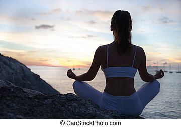 Woman meditating in a yoga pose on the beach