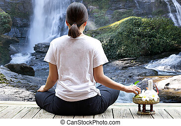 Woman meditating in forest with waterfall flower