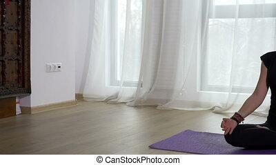 Woman meditating in lotus pose in a yoga studio