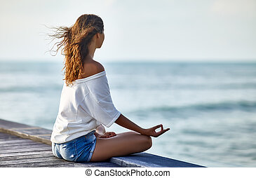 Woman meditating in Lotus Pose on pier with the sea view....