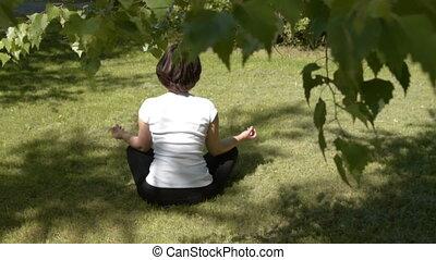 Woman meditating in lotus pose outdoors