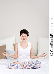 Woman Meditating In Lotus Position On Bed