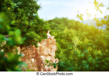 woman meditating in sitting yoga position on the top of a