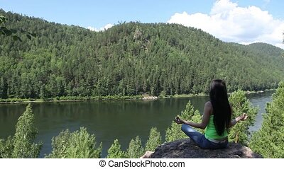 Woman meditating in lotus posture doing yoga on top of the mountain on a rock.