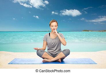 woman meditating in lotus yoga pose on beach