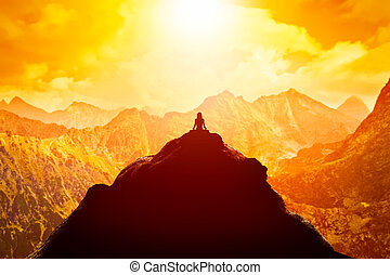 Woman meditating in sitting yoga position on the top of a mountains above clouds at sunset.
