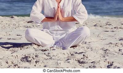 Woman meditating in sukhasana pose