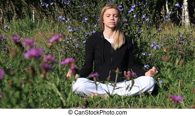 Woman meditating in the city park
