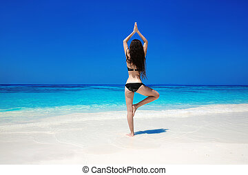 Woman meditating in tree yoga position on the exotic beach. Zen, meditation, peace. Balance. Young female relax. Wellness. Bliss freedom concept.