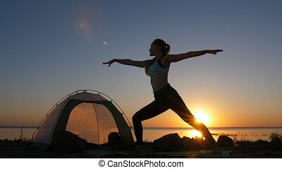 Woman meditating in warrior pose at sunset
