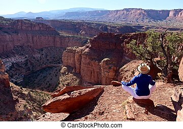 Woman Meditating in Yoga Pose at the Edge of Canyon.