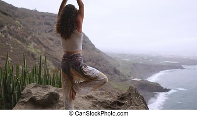 Woman meditating in yoga warrior pose at the ocean, beach...