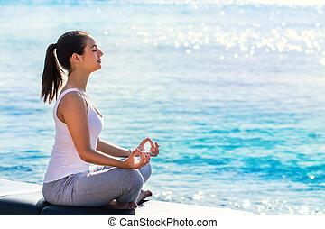 Woman meditating next to sea.