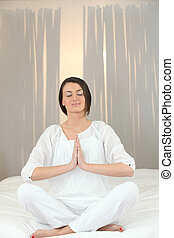 Woman meditating on a bed