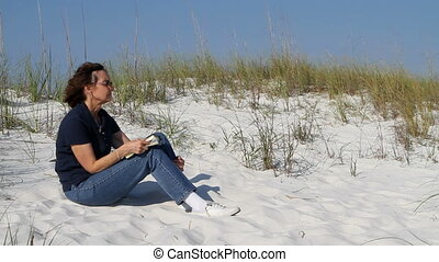 Woman Meditating On Dune - Mature woman sits on a sand dune...
