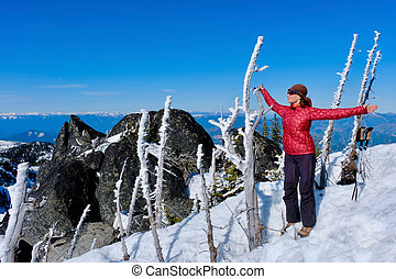 Woman meditating on mountain top.