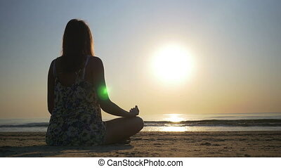 Woman meditating on the beach towards the sea