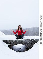 woman meditating on the stone bridge