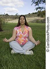 Woman meditating - Pregnant woman meditating on grass