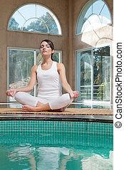 Woman meditating sitting in lotus position