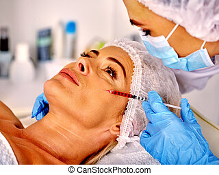 Woman middle-aged in spa salon with beautician. Female giving botox injections.