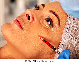 Woman middle-aged in spa salon with beautician. Woman giving botox injections.