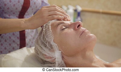 Woman middle-aged take face and neck lymphatic, drainage massage in spa salon