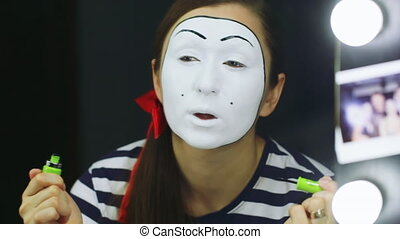 Woman mime does makeup near the mirror