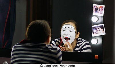 Woman mime lipstick in the mirror