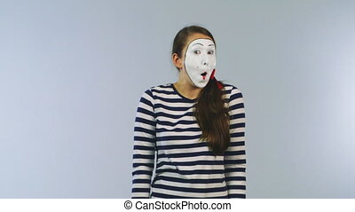 Woman mime shows a sign advertising