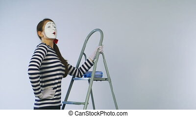 Woman mime standing on a ladder and paint the invisible wall