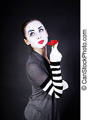 woman mime with theatrical makeup and red flower in hands