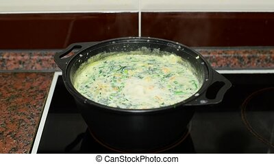 Woman mixes cheese soup in a saucepan on stove
