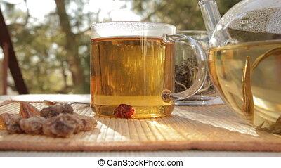 Woman mixes glass of tea outdoors