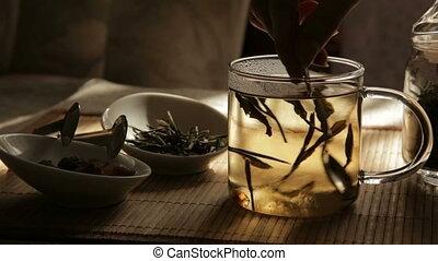 Woman mixes glass of tea