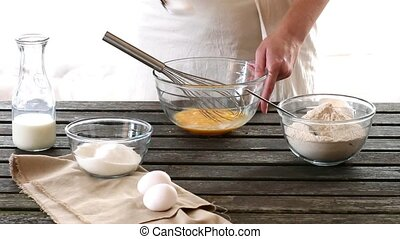Woman mixes ingredients for sponge cake. Rustic style.