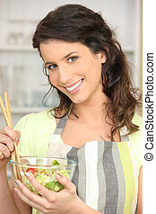 Woman mixing bowl of salad leaves