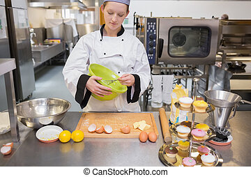 Woman mixing dough in kitchen while looking concentrated