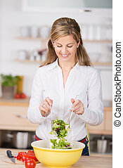 Woman Mixing Salad In Kitchen