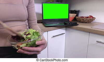 Woman mixing salads in bowl close up near laptop PC with...