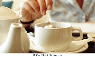 Woman Mixing sugar in a cup of tea