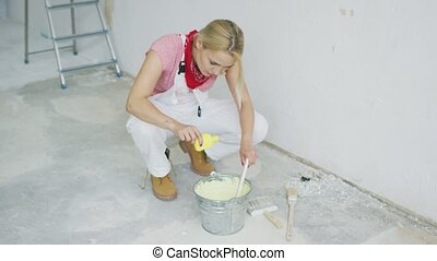 Woman mixing wall paint in bucket - Young blond female in...