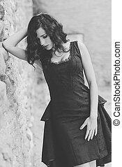 Woman, model of fashion, wearing black dress with curly hair