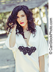 Woman, model of fashion, wearing white dress with curly hair