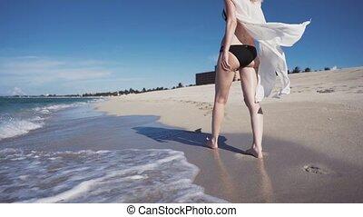 woman model walking on the beach The beautiful blonde in a bikini walking on the beach